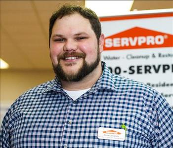 headshot of male with dark hair in front of a SERVPRO sign