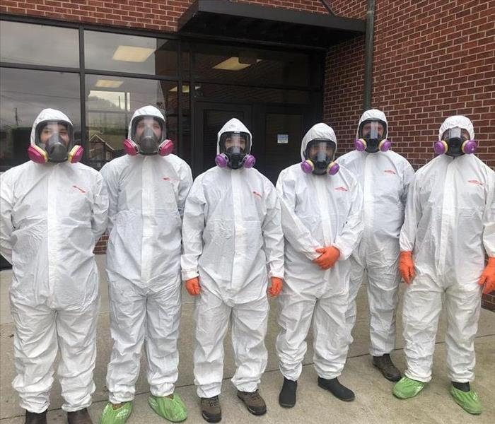 SERVPRO employees in hazmat suits cleaning