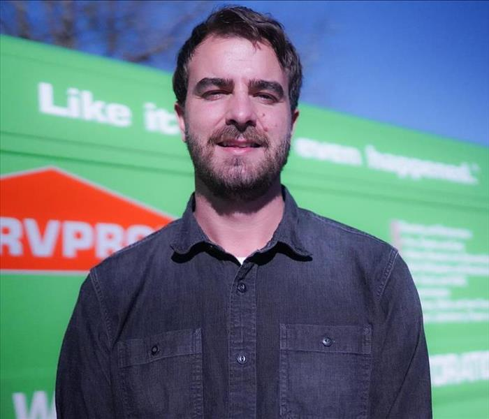 A headshot of a male in a jean shirt in front of a SERVPRO van